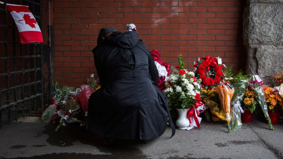 A man places flowers in memory of soldier Nathan Cirillo outside the gates of the John Weir Foote Armoury, the home of the Argyll and Sutherland Highlanders of Canada in Hamilton, Ont., Wednesday, Oct. 22, 2014. (Aaron Lyn / THE CANADIAN PRESS)