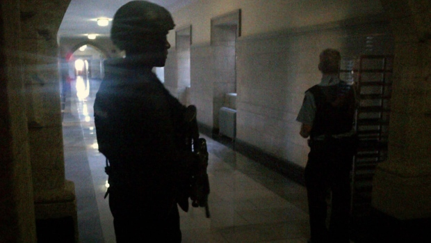 A heavily armed officer guards the halls of Parliament Hill in Ottawa, Wednesday afternoon, Oct. 22, 2014.
