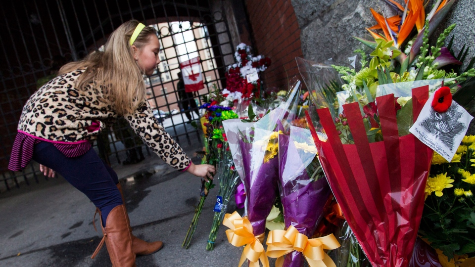 Chloe Hogan, of Hamilton, places flowers in memory of soldier Nathan Cirillo outside the gates of the John Weir Foote Armoury, the home of the Argyll and Sutherland Highlanders of Canada in Hamilton, Ont., Wednesday, Oct. 22, 2014. (Aaron Lynett / THE CANADIAN PRESS)