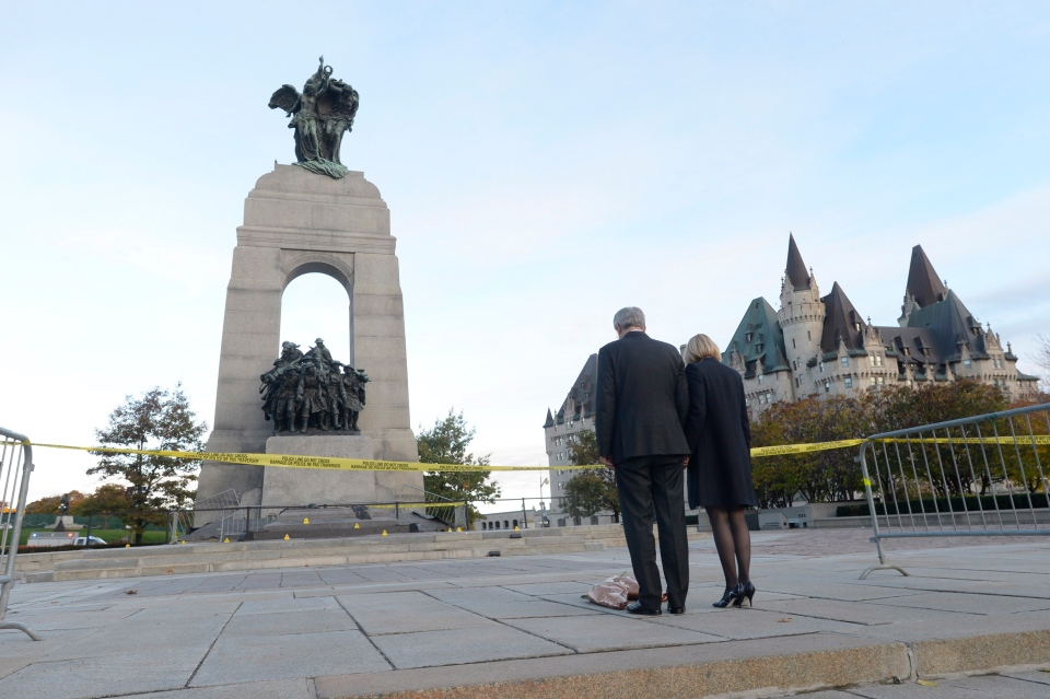 Prime Minister Stephen Harper and wife Laureen leave flowers on the perimetre of the crime scene at the National War Memorial in Ottawa on Thursday, Oct. 23, 2014. (Adrian Wyld / THE CANADIAN PRESS)