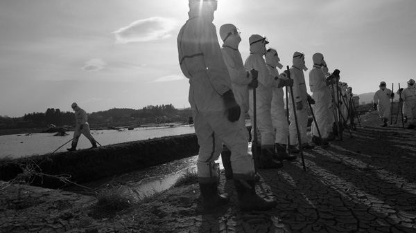 Japanese police wearing protective radiation suits search for the bodies of victims of the tsunami in the Odaka area of Minamisoma, Thursday, April 7, 2011. (AP / David Guttenfelder)