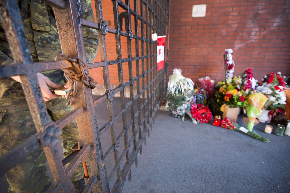 A soldier at The Lieutenant-Colonel John Weir Foote Armoury in Hamilton, Ont. locks the gates after allowing another soldier to enter on Thursday, Oct. 23, 2014. (Peter Power / THE CANADIAN PRESS)