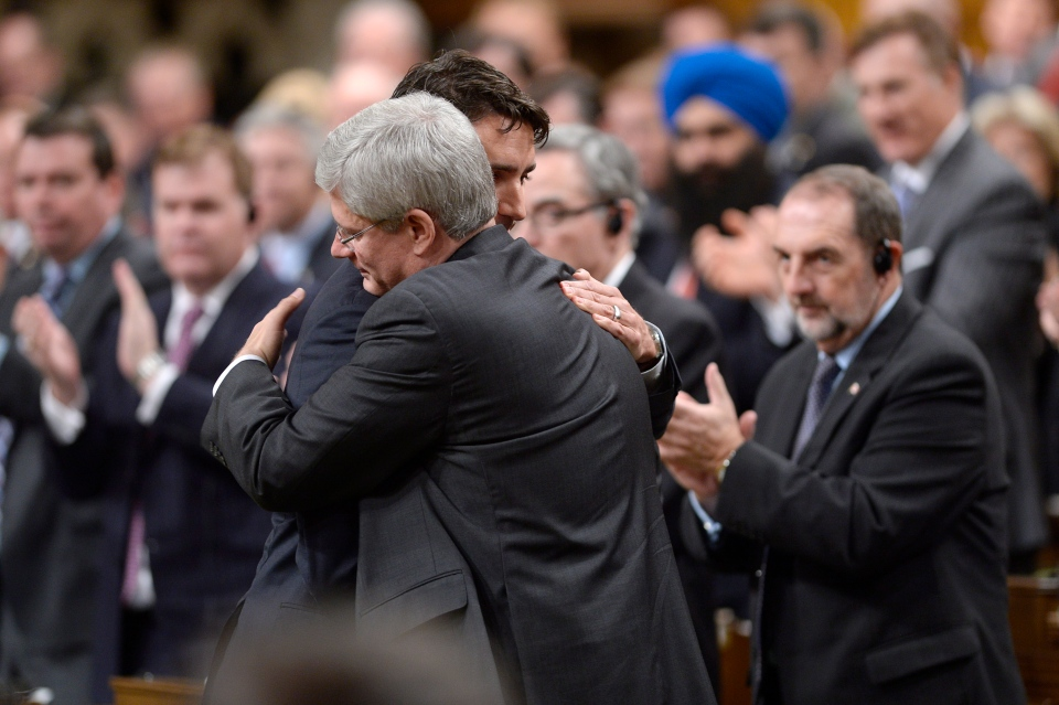 Prime Minister Stephen Harper hugs the leader of the Liberal Party of Canada Justin Trudeau in the House of Commons, Thursday, Oct. 23, 2014. (Adrian Wyld / THE CANADIAN PRESS)
