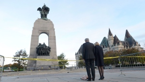 Prime Minister Stephen Harper and wife Laureen walk away after leaving flowers on the perimeter of the crime scene at the National Memorial in Ottawa on Thursday Oct. 23, 2014. (Adrian Wyld / THE CANADIAN PRESS)