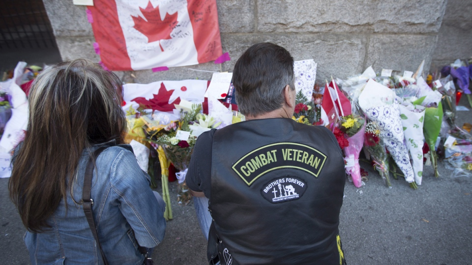 A veteran of 3 RCHA, Robert Lupton, and his friend, Brenda Dimas, left, pay their respects at a makeshift memorial to Cpl. Nathan Cirillo at The Lieutenant-Colonel John Weir Foote Armoury in Hamilton, Ont. on Thursday, Oct. 23, 2014. (Peter Power / THE CANADIAN PRESS)