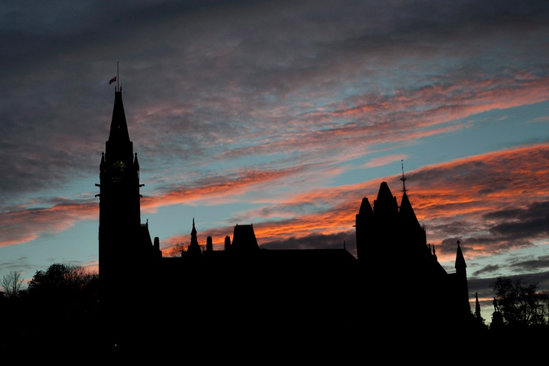 The Canadian flag flies at half mast atop the Peace Tower on Parliament Hill at sunset in Ottawa, on Thursday, Oct. 23, 2014. (The Canadian Press/Justin Tang)
