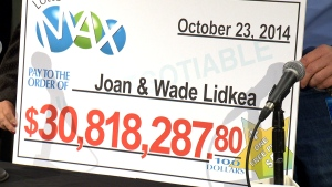 Joan and Wade Lidkea hold up their giant cheque after it was announced they won an almost $31 million Lotto Max jackpost.