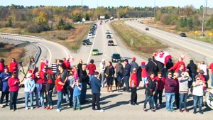 Dozens gather as the body of the soldier fatally shot at the National War Memorial travels along the Highway of Heroes Friday, Oct. 24, 2014.