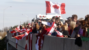 Crowds wait on an overpass at the Veterans Memorial Highway for a procession transporting the body of Cpl. Nathan Cirillo to pass by in Ottawa on Friday, Oct. 24, 2014. (Patrick Doyle / THE CANADIAN PRESS)
