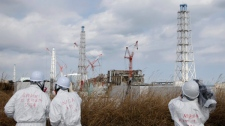 Members of the media wearing protective suits and masks report, escorted by an official of Nuclear and Industrial Safety Agency, second left, at Tokyo Electric Power Co.'s tsunami-crippled Fukushima Dai-ichi nuclear power plant in Fukushima prefecture, northeastern Japan, Monday, Feb. 20, 2012. (AP / Issei Kato)