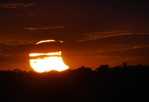 The sun breaks though a heavy cover of clouds at sunset Thursday, Oct. 23, 2014, revealing a partial solar eclipse as seen from Westminster, Md. (AP / The Carroll County Times, Dylan Slagle)