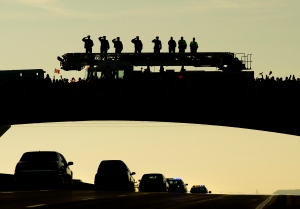 Supporters pay tribute as the body of Cpl. Nathan Cirillo is transported in a hearse from Ottawa to Hamilton, along the Highway of Heroes in Port Hope, Ont., on Friday, Oct. 24, 2014. (Nathan Denette / THE CANADIAN PRESS)