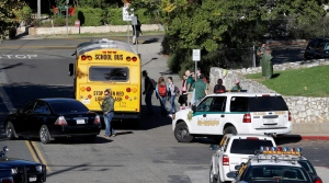 Placer High School students board a bus as law enforcement officers stand guard in Auburn, Calif., Friday, Oct. 24, 2014. The school had been locked down as authorities worked to apprehend Marcelo Marquez, 34, who was barricaded in a nearby home. (AP / Rich Pedroncelli)