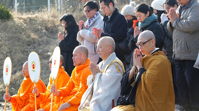 Buddhist monks and tsunami survivors offer prayers in the earthquake and tsunami-devastated city of Kesennuma, Iwate Prefecture, northeastern Japan, Sunday, March 11, 2012. (AP / Koji Sasahara)