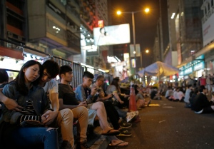 A pro-democracy couple take a rest on a main road in the occupied area of the Mong Kok district Hong Kong Saturday, Oct. 25, 2014. Pro-democracy protesters in Hong Kong plan to hold a spot referendum Sunday on whether to stay in the streets or accept government offers for more talks and clear their protest camps. (AP Photo/Vincent Yu)