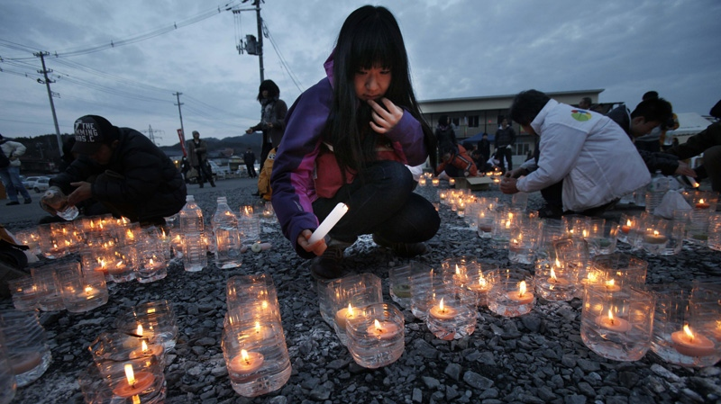 A girl lights candles in front of a temporary shopping complex in the earthquake and tsunami-devastated city of Kesennuma, Iwate prefecture, northeastern Japan, Sunday, March 11 2012, to mark the first anniversary of the massive disaster that devastated Japan's northeast one year ago. (AP Photo/Koji Sasahara)