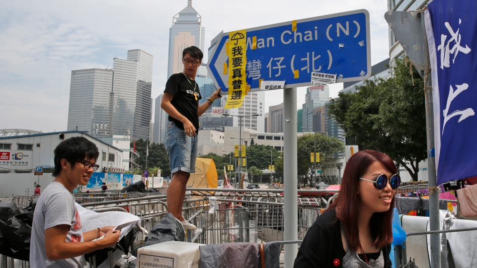 "A protester hangs a yellow placard with the words ""I want genuine universal suffrage"" on a road signboard at the occupied areas outside the government headquarters in Hong Kong's Admiralty, Sunday, Oct. 26, 2014. (AP / Kin Cheung)"