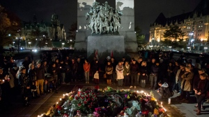 The Tomb of the Unknown Soldier at the National War Memorial is surrounded by people during a candlelight vigil in Ottawa on Saturday, Oct. 25, 2014. People gathered in tribute of Cpl. Nathan Cirillo, 24, a reservist from Hamilton, Ontario, who was killed on Wednesday. (Justin Tang / THE CANADIAN PRESS)