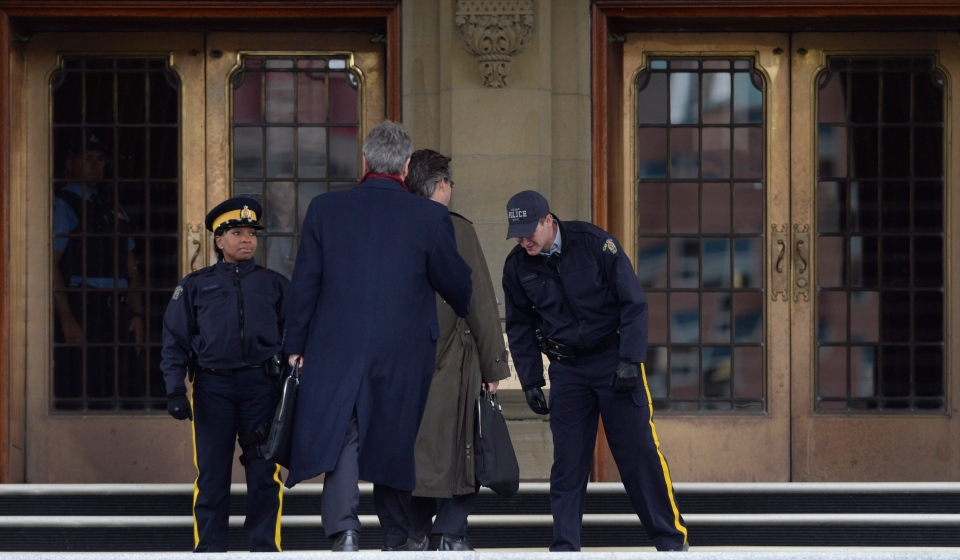 RCMP officers check identification passes of visitors, an additional security measure, on Parliament Hill in Ottawa on Thursday, Oct. 23, 2014. (CP / Adrian Wyld)