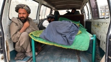 An Afghan man sits in the back of a bus with the body of a person who was allegedly killed by a U.S. service member in Panjwai, Kandahar province south of Kabul, Afghanistan, Sunday, March 11, 2012. (AP / Allauddin Khan)