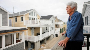 Anne Hoerning looks from her second floor balcony at new houses that have been built in the Breezy Point section of the Queens borough of New York, Oct. 15, 2014. (AP / Mark Lennihan)