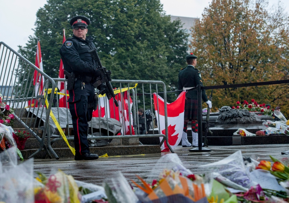 A heavily armed Ottawa Police officer stands in front of sentries guarding the Tomb of the Unknown Soldier at the National War Memorial in Ottawa on Saturday, Oct. 25, 2014. (Justin Tang / THE CANADIAN PRESS)