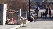 Steven Anderson reads a book and enjoys the sunshine on a bridge at Cedarvale Park in Toronto on Sunday, March 11, 2012. (Pawel Dwulit / THE CANADIAN PRESS)