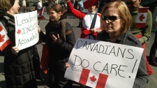 "A protester holds up a sign at a rally condemning so-called ""robocalls"" in Toronto on March 11, 2012."