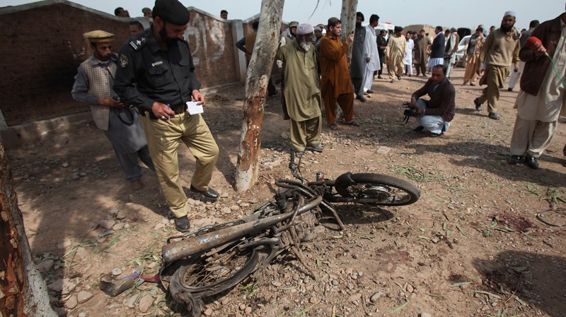 A Pakistani police officer examines a damaged motorcycle at the site of suicide bombing in Badhber area on the outskirts of Peshawar, Pakistan on Sunday, March 11, 2012. (AP Photo/Mohammad Sajjad)
