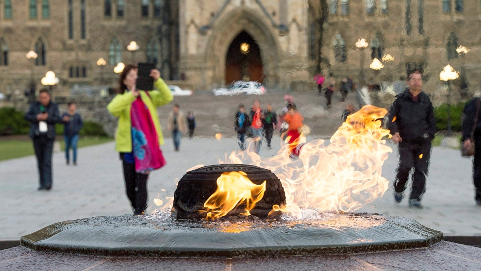 Visitors walk past the Centennial Flame on Parliament Hill in Ottawa, Ontario, Saturday, Oct. 25, 2014. (Justin Tang / THE CANADIAN PRESS)
