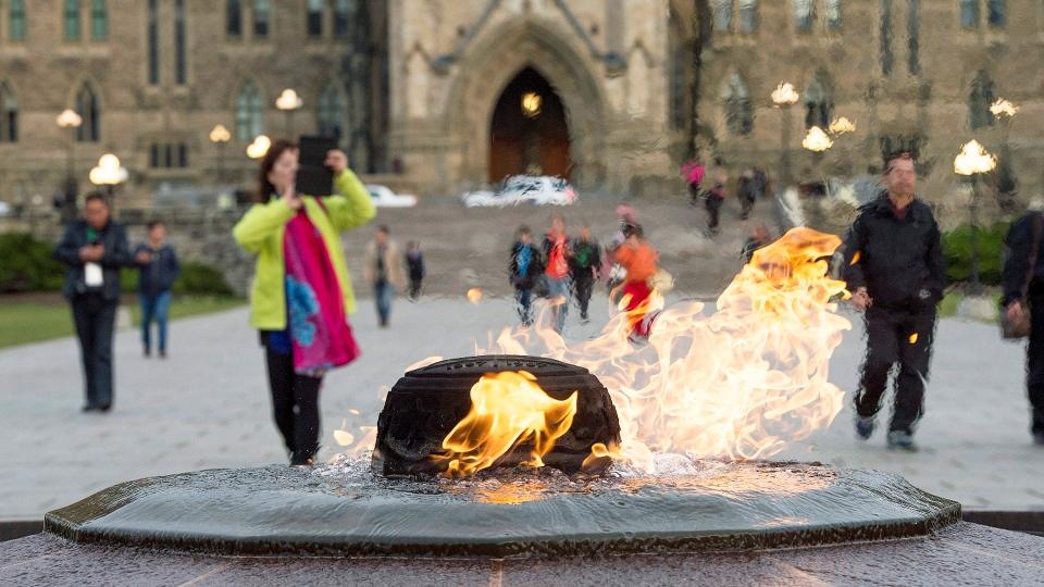 Visitors walk past the Centennial Flam