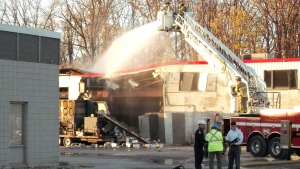 Firefighters pour water on a building at Veolia ES Canada Industrial Services Inc. plant to prevent hot spots in Sarnia, Ontario on Saturday Oct. 25, 2014. (Colin Graf / THE CANADIAN PRESS)
