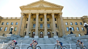 Cyclists ride past the Alberta Legislature in Edmonton, on Saturday, Aug. 30, 2014. (Jason Franson / THE CANADIAN PRESS)