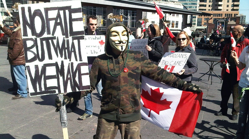 A group of protesters holds up signs at a rally condemning so-called 'robocalls' in Toronto on March 11, 2012. (Ashley Rowe / CTV Toronto)