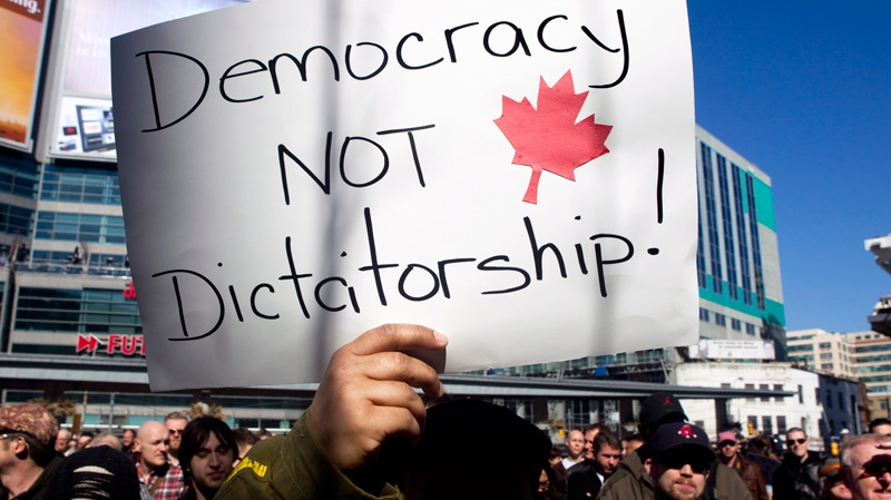 Protesters listen to a speaker at a demonstration in Toronto on Sunday, March 11, 2012. (Chris Young / THE CANADIAN PRESS)