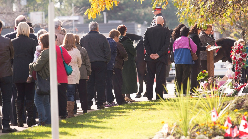 People wait in line to sign the book of condolences and attending the public visitation for Cpl. Nathan Cirillo at the Markey-Dermody Funeral Home in Hamilton, Ontario on Monday, Oct. 27, 2014. (Peter Power / THE CANADIAN PRESS)