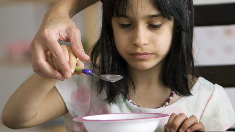 In this Feb. 20, 2009 file photo, 6-year-old Zola Leonard, a patient at the pediatric feeding program at the Montreal Children's Hospital, eats some cereal at her home in Longueuil. Que. (THE CANADIAN PRESS/Ryan Remiorz)