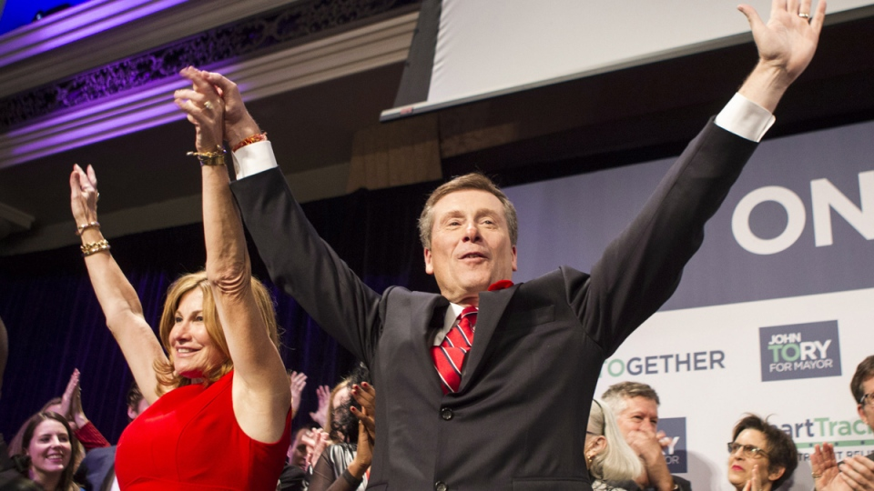Newly-elected Mayor John Tory, right, stands with his wife Barbara Hackett as he waves to supporters at a rally after winning the municipal election in Toronto on Monday, Oct., 27, 2014. (Chris Young / THE CANADIAN PRESS)