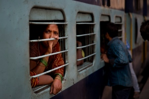 A woman looks outside from a window of a train crowded with people trying to reach their homes ahead of Hindu festival Chhath Puja at a railway station in New Delhi, India, Tuesday, Oct. 28, 2014. (AP / Bernat Armangue)