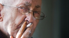 Jean Yves Blais smokes at his home in St. Hubert near Montreal, Friday, March 9, 2012. (Graham Hughes / THE CANADIAN PRESS)