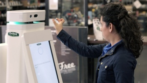 In this undated image provided by Lowe's, a woman holds a nail up to be scanned by an OSHbot robot. (AP / Lowe's)