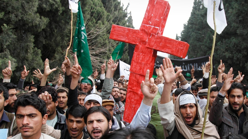 Demonstrators chant anti U.S. slogans as they carry a red cross following Sunday's killing of civilians in Panjwai, Kandahar by a U.S. soldier during a protest in Jalalabad east of Kabul, Afghanistan, Tuesday, March 13, 2012. (AP / Rahmat Gul)