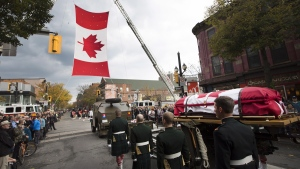 The body of Cpl. Nathan Cirillo is escorted through the streets toward his funeral service in Hamilton, Ont., on Tuesday, Oct. 28, 2014. (Peter Power / THE CANADIAN PRESS)