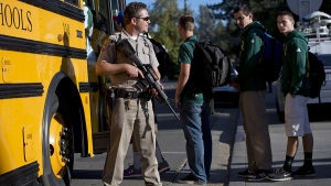 A California Highway Patrol officer guards Placer High School students as they enter a bus following a lock down after the search for a suspect, in Auburn, Calif., Friday, Oct. 24, 2014. (AP / The Sacramento Bee, Hector Amezcua)