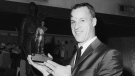 Detroit Red Wings' star Gordie Howe, wearing a prominent bruise over his right eye, compares miniature trophy he received with the large statue in New York, Feb. 20, 1967, after he received the Lester Patrick Memorial Trophy for long and meritorious service to the sport in the U.S. (AP / Dave Pickoff)