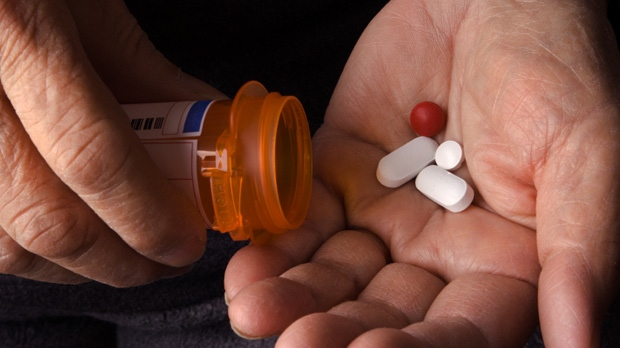 A person pours pills into their hand.