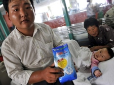 The uncle of fifteen-month-old Tian Yaowen from Henan province, who is suffering from kidney stones, shows a bag of Sanlu infant formula in a hospital in Wuhan in central China's Hubei province Saturday Sept. 13, 2008.(AP)