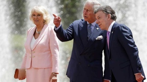 Prince Charles talks to Colombia's President Juan Manuel Santos as his wife Camilla the Duchess of Cornwall stands by during a welcoming ceremony at the presidential palace in Bogota, Colombia, Wednesday, Oct. 29, 2014. (AP / Fernando Vergara)