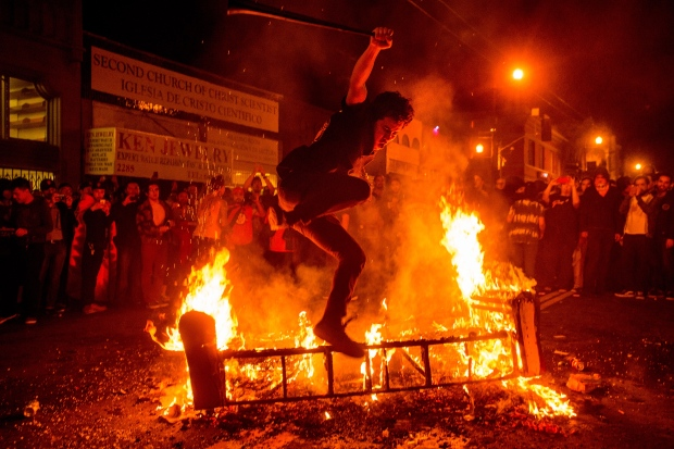 A man jumps over a burning couch in the Mission district after the San Francisco Giants defeated the Kansas City Royals to win the World Series on Wednesday, Oct. 29, 2014, in San Francisco. (AP / Noah Berger)