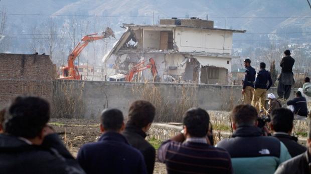 Pakistani media film as authorities use heavy machinery to demolish the compound of Osama bin Laden in Abbottabad, Pakistan on Sunday, Feb. 26, 2012. (AP / Anjum Naveed)